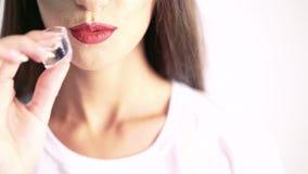 Schließen Sie oben von beißendem Eiswürfel der Frau auf beige Hintergrund stock video footage
