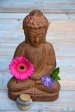 Schließen Sie oben von braunem Buddha auf benutztem Holz mit Zensteinen und -blumen Lizenzfreie Stockfotografie