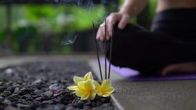 Schließen Sie oben von brennenden Räucherstäbchen mit gelben Blumen auf Steinboden draußen stock video footage