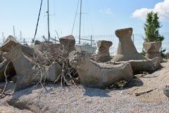 Schließen Sie oben von den alten und defekten tetrapods, die vom Beton gemacht werden, der herein begraben wird Stockfoto