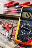 Schließen Sie oben von den Arbeitswerkzeugen auf elektrischen Installationen, auf einem antiken Holztisch lizenzfreie stockfotografie