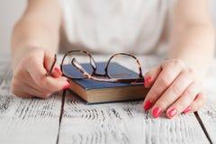 Schließen Sie oben von den Augengläsern auf Lehrbuch in der Bibliothek getrennte alte Bücher Lizenzfreie Stockfotos