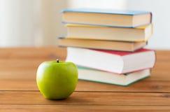 Schließen Sie oben von den Büchern und vom grünen Apfel auf Holztisch Stockfotografie