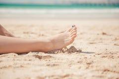 Schließen Sie oben von den Beinen der Frauen auf dem Strand Stockfotos