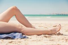 Schließen Sie oben von den Beinen der Frauen auf dem Strand Stockfoto