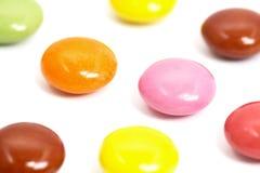 Schließen Sie oben von den bunten Schokoladen auf weißem Hintergrund Lizenzfreies Stockfoto