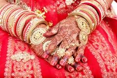 Schließen Sie oben von den dekorativen Händen der indischen Braut mit goldenem Schmuck lizenzfreies stockfoto