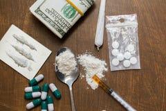 Schließen Sie oben von den Drogen, vom Geld, vom Löffel und von der Spritze Lizenzfreie Stockfotografie