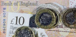 Schließen Sie oben von den ein Pfund-Münzen auf einer zehn Pfund-Anmerkung - britische Währung Lizenzfreies Stockbild