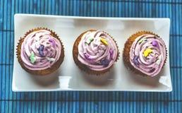 Schließen Sie oben von den Erdbeerrosakleinen kuchen auf weißer Platte auf blauer hölzerner Matte Lizenzfreies Stockbild