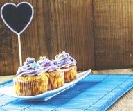 Schließen Sie oben von den Erdbeerrosakleinen kuchen auf weißer Platte auf blauer hölzerner Matte Lizenzfreies Stockfoto