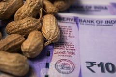 Schließen Sie oben von den Erdnüssen oder von den Erdnüssen mit indischer Währung unten auf lokalisiertem Hintergrund stockbild