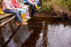 Schließen Sie oben von den Füßen der Kinder, die von der Holzbrücke baumeln stockfotografie