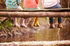 Schließen Sie oben von den Füßen der Kinder, die von der Holzbrücke baumeln lizenzfreies stockfoto