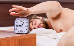Schließen Sie oben von den Füßen in einem Bett unter weißer Decke Netter junger Mann wacht auf, nachdem er morgens geschlafen hat stockbilder