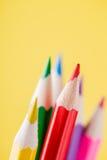 Schließen Sie oben von den Farbbleistiften mit unterschiedlicher Farbe über gelbem Hintergrund Stockfotos