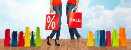 Schließen Sie oben von den Frauen mit Verkaufszeichen auf Einkaufstasche Lizenzfreies Stockbild