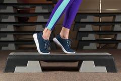 Schließen Sie oben von den Frauen-tragenden weißen Turnschuhen, die Toe Tap auf Schritt-Plattform in aerobem tun stockbilder
