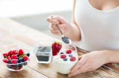 Schließen Sie oben von den Frauenhänden mit Jogurt und Beeren Lizenzfreie Stockfotos