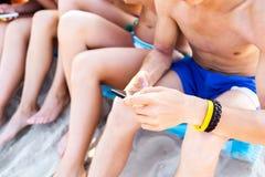 Schließen Sie oben von den Freunden mit Smartphones auf Strand Stockfoto