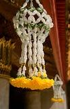 Schließen Sie oben von den gelben Blumen, die vom Dach einer Pagode hängen stockfoto