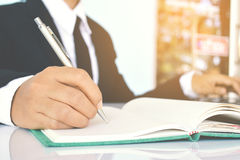 Schließen Sie oben von den Geschäftsfrauen, die auf blauen Hintergrund schreiben Stockbild