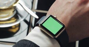 Schließen Sie oben von den Geschäftsmannhänden mit smartwatch grünem Schirm-Farbenreinheitsschlüssel Gemütliches Café im Hintergr stock footage