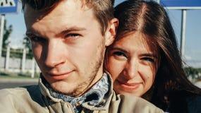 Schließen Sie oben von den glücklichen emotionalen Paaren, die auf backgr umarmen und blinzeln Stockfoto