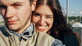 Schließen Sie oben von den glücklichen emotionalen Paaren, die auf backgr umarmen und blinzeln Lizenzfreies Stockfoto