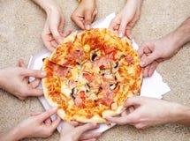 Schließen Sie oben von den glücklichen Freunden, die zu Hause Pizza essen Lizenzfreie Stockfotos