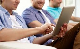 Schließen Sie oben von den glücklichen Freunden mit Tabletten-PC zu Hause Stockfotografie