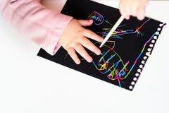 Schließen Sie oben von den glücklichen Mädchenhänden, die auf buntes Malereipapier des magischen Kratzers mit Zeichnungsstock zei stockfotografie