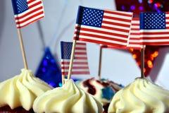 Schließen Sie oben von den glasig-glänzenden kleinen Kuchen oder von Muffins, die mit ameri verziert werden Lizenzfreies Stockfoto