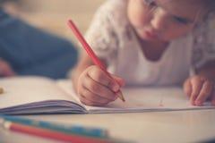 Schließen Sie oben von den Händen bemuttern ein kleines Mädchen, das zusammen schreibt lizenzfreies stockfoto