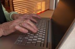 Schließen Sie oben von den Händen der älteren Frau, die an Computertastatur arbeiten lizenzfreies stockbild