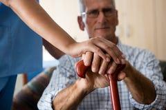 Schließen Sie oben von den Händen der Ärztin und des älteren Mannes, die gehenden Stock halten stockfotos