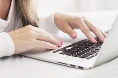 Schließen Sie oben von den Händen der Frau, die mit Laptop im Bett flacher DOF schreiben Lizenzfreie Stockfotografie