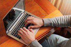 Schließen Sie oben von den Händen des Mannes, die an Laptop im klassischen Artluxusinnenraum arbeiten Stockbild
