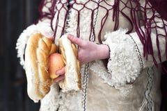 Schließen Sie oben von den Händen, die Apfel und Brezel eines Kindes anhalten, das in der traditionellen rumänischen Abnutzung gek Stockbilder