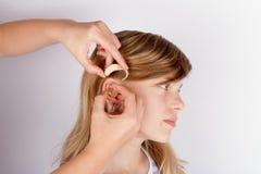 Schließen Sie oben von den Händen, die ein Hörgerät in Ohr einfügen stockbilder