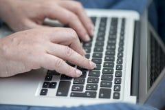 Schließen Sie oben von den Händen einer Frau mit einem Laptop Lizenzfreie Stockfotografie