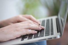 Schließen Sie oben von den Händen einer Frau mit einem Laptop Stockfoto
