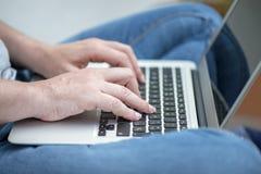 Schließen Sie oben von den Händen einer Frau mit einem Laptop Lizenzfreies Stockbild