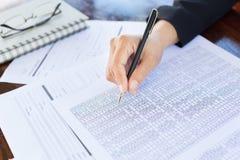 Schließen Sie oben von den Händen einer Geschäftsfrau in eine Klage Unterzeichnen oder wr Lizenzfreie Stockfotos