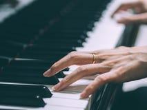 Schließen Sie oben von den Händen einer jungen Frau, die Klavier spielt, selektiv Lizenzfreies Stockbild