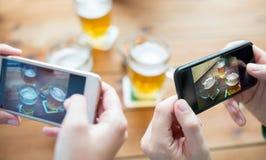Schließen Sie oben von den Händen mit dem Smartphone, der Bier darstellt Lizenzfreies Stockbild