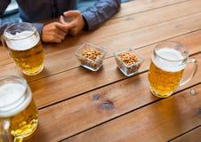 Schließen Sie oben von den Händen mit den Bierkrügen an der Bar oder an der Kneipe Stockfotografie