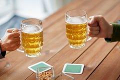 Schließen Sie oben von den Händen mit den Bierkrügen an der Bar oder an der Kneipe Lizenzfreies Stockbild