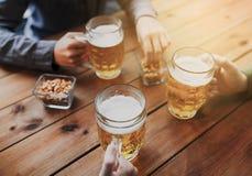 Schließen Sie oben von den Händen mit den Bierkrügen an der Bar oder an der Kneipe Lizenzfreie Stockfotografie