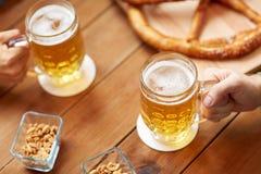 Schließen Sie oben von den Händen mit den Bierkrügen an der Bar oder an der Kneipe Stockfotos